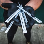 Gloved tattoo artist holds six tattoo needles.