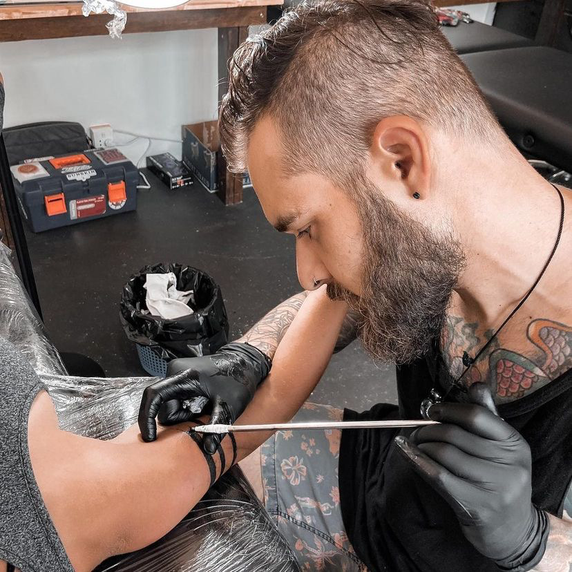 Brentan Wolf, a stick and poke artist from Australia, hand poking a tattoo on a client.